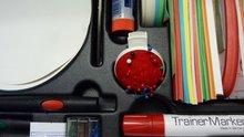 Inhalt eines Moderationskoffers, bestehend aus Schere, Klebestift, Pinnnadeln, Nadelkissen, Moderationskarten und Moderationsstiften