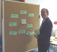 lachender Teilnehmer steht an der Pinnwand, an der bereits einige Zettel geheftet sind